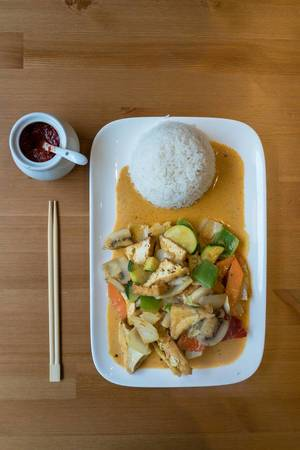 Red thai-curry with vegan tofu bits, zucchini, pepper, carrots and zucchini on a plate with rice, chop-sticks and a jar with chili paste on a wooden table - top view
