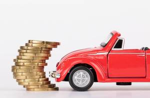 Red toy car with stack of coins on white background