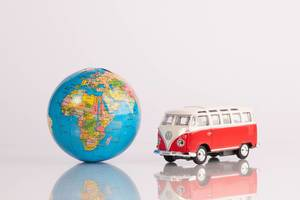 Red vintage camper van with globe