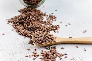 Reddish-brown linseed or flaxseed, poured from a glass jar on a white wooden table and on a wooden spoon