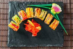 Regenbogen-Drachen-Sushirolle mit Wasabi und Ingwer geschnitten auf schwarzer Steinplatte