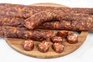 Regionale, selbstgemachte Wurst aus Schweinefleisch, auf einem Küchenbrettchen