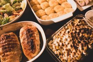 Reiche Auswahl an Speisen in Auflaufformen für das Thanksgiving-Essen mit Truthahn, mit Marshmallows überbackenes Gemüse und gemischtem Salat