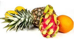 Reife exotische und Zitrusfrüchte, unter anderem Pitaya, Ananas und Orange, vor weißem Hintergrund