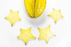 Reife Karambole und Scheiben der Sternfrucht auf einem weißen Tisch