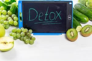Reife Kiwis, Gurken, Weintrauben, Äpfel und Salat, neben dem Wort Detox - Entschlackung, auf einem weißen Küchentisch