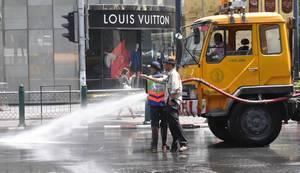 Reinigung einer Straße in Thailand, Louis Vuitton Shop im Hintergrund