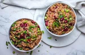 Reis mit roten Bohnen und Frühlingszwiebel in zwei Schüsseln, Aufnahme von oben