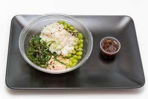 Reis mit Seealgensalat, Sojabohnen und Lachscreme in Plastikschale und Soße auf Teller