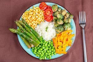 Reis mit Spargel, Erbsen, Mais, Karotten, Tomaten und Rosenkohl auf einem Teller mit Gabel Draufsicht