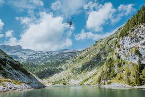 Rescue helicopter flying above Krn lake