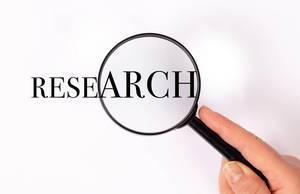 Research unter der Lupe auf weißem Hintergrund