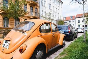 Retro-Auto und originaler, oranger VW Beetle in einer deutschen Stadt geparkt