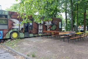 Retro-Bus voll von bunten Graffities mit Biertische im Vordergrund im BaseCamp Hostel in Bonn