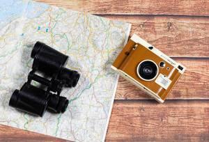 Retro-Kamera und Fernglas auf einer Landkarte