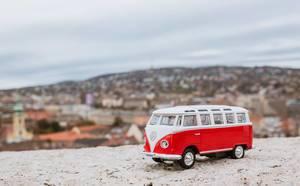 Retro-Spielzeugauto von VW auf der Mauer der Burg von Buda, im Hintergrund Budapest in Unschärfe