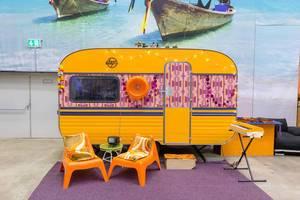 Retro-Wohnwagen mit lila Teppich, zwei orangen Sessel und einem Synthesizer im Vordergrund