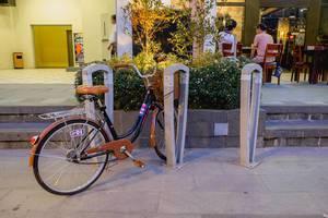 Retrofahrrad mit Korb, in einer Gasse an einem Fahrradständer geparkt