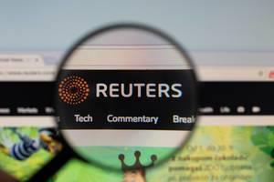 Reuters-Logo am PC-Monitor, durch eine Lupe fotografiert