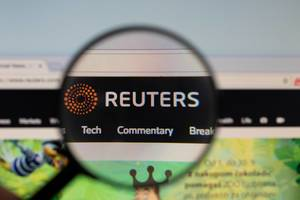 Reuters logo on a computer screen with a magnifying glass