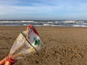 Reversed plastic bottle at the beach shows pollution