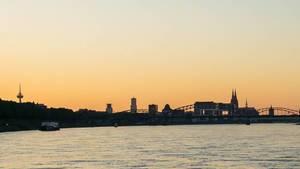 Rhein in Köln bei Sonnenuntergang. Kölner Dom in der Ferne