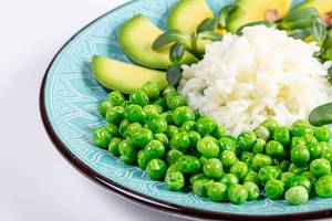 Rice with fresh avocado, green peas and sunflower microgreens