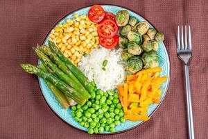 Rice with vegetables on a brown kitchen towel with a fork, top view