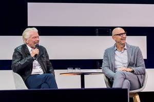 Richard Branson and Tim Höttges look at the stage and smile