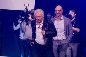 Richard Branson runs on stage at DigitalX in Cologne