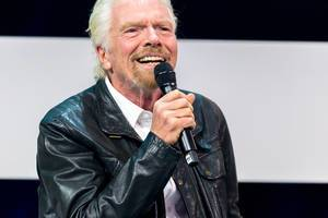 Richard Branson smiles to the audience and talks at Digital X in Cologne