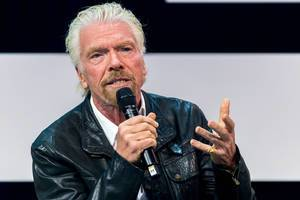 Richard Branson with a microphone speaking close up