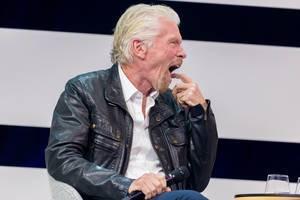 Richard Branson yawning on stage of Digital X