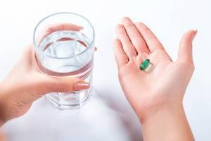 Richtige Einnahme von Medikamenten – Frau hält Tablette und Wasserglas in Händen