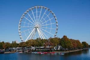 Riesenrad, Bäume und Fluss in der Stadt an einem sonnigen Herbsttag