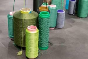 Riesige Spulen mit Faden für industrielle Verarbeitung und Produktion auf Boden