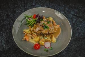 Rinderfilet bunt garniert mit Tomate, Radieschen, Kresse, Waldpilzen, Gurke, Salat und Kartoffeln auf grauen Keramikteller - Nahaufnahme