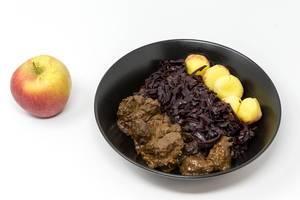 Rindergulasch nach traditioneller Art mit Apfelrotkohl und Miniknödel mit einem Apfel auf weißem Hintergrund