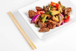 Rindfleisch mit Gemüse und scharfer Sauce, neben Essstäbchen aus der Sicht von oben