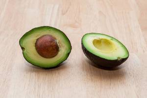 Ripe Avocado cut in half on a wooden background