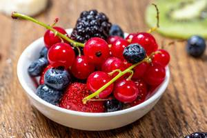 Ripe berries in a bowl on a wooden table