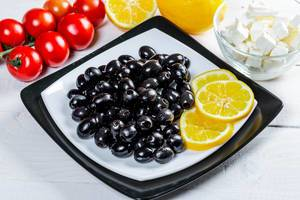 Ripe black olives with feta cheese, lemon and vegetables  Flip 2019