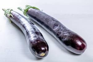 Ripe eggplant on white wooden background