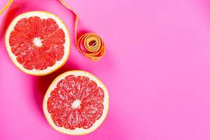 Ripe half of pink grapefruit citrus fruit on pink background with measuring tape