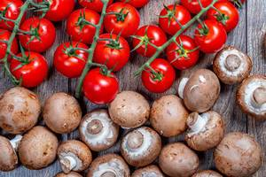 Ripe red tomatoes on branches with brown fresh mushrooms (Flip 2019)