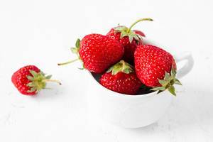 Ripe strawberries in a tea cup on white background
