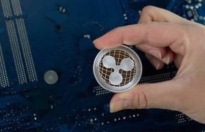 Ripple XRP Münze zwischen den Fingern