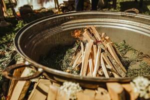 Rituelles Lagerfeuer in einer großen Schale mit Pflanzen und Holz