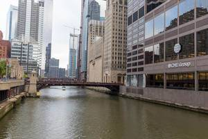 Riverside and building with logo of the CME Group, bridge and skyscrapers in the central business district of Chicago, The Loop