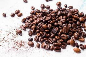 Roasted coffee beans lying loosely on a white surface